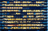 """Lots of people working late. Employees seen as silhouettes against their brightly lit offices with large windows. Building framed by the """"blue hour"""" evening sky"""