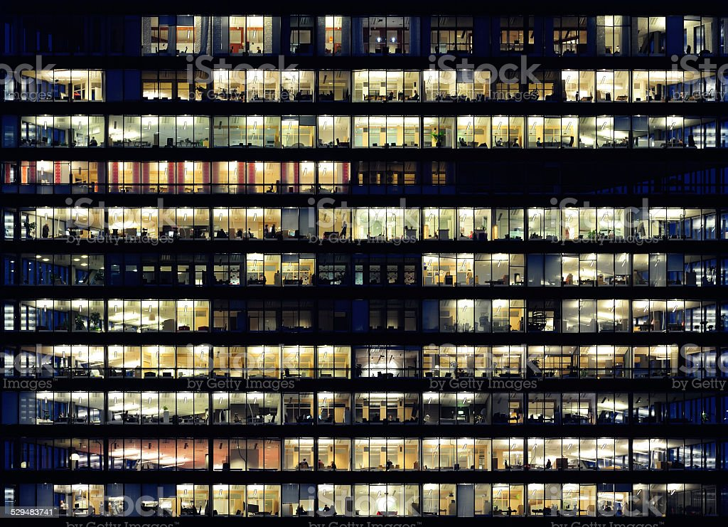 Workers working late. Office windows by night. bildbanksfoto