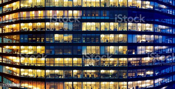 Photo of Workers working late. Sunset to the left. Blue hour. Curved building