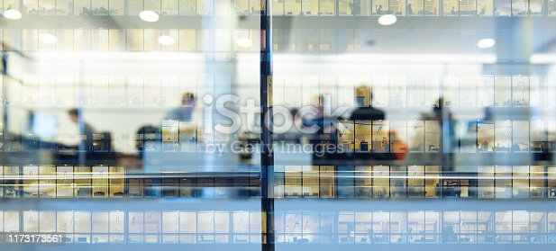 istock Workers working late. Tall building reflected 1173173561
