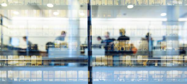 trabalhadores trabalhando até tarde. edifício alto refletido - arranha céu - fotografias e filmes do acervo