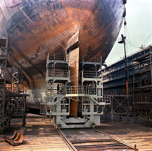 Workers working on a big ship while docked stock photo