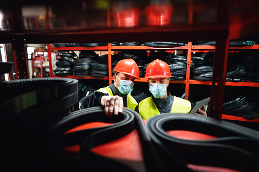 Two young men, engineers or factory workers, with protective face masks doing stock control by using a digital tablet in a warehouse of endless rubber bands and belts.