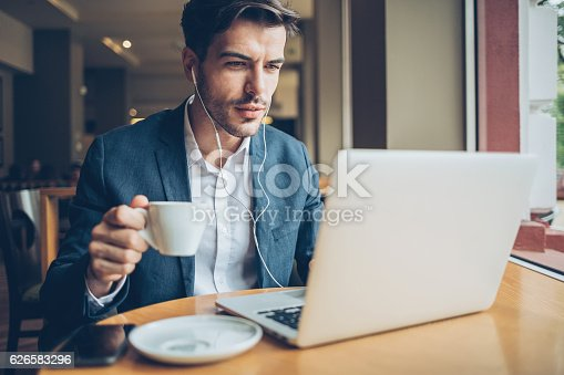 Smiling man with headphones working on a laptop and drinking coffee