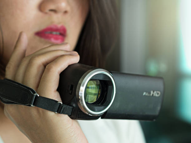 Working Asian woman recording or taking a media video using video recorder, camcorder or video camera, close up face and hand stock photo