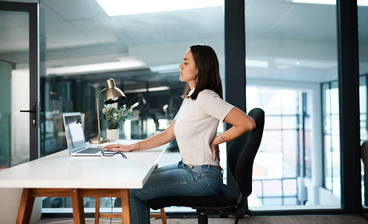 Shot of a young businesswoman experiencing back pain while working in an office
