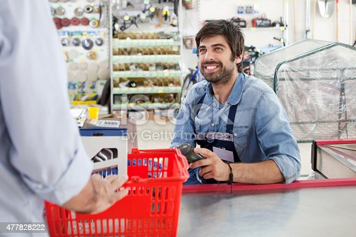 Man working at till point in hardware store