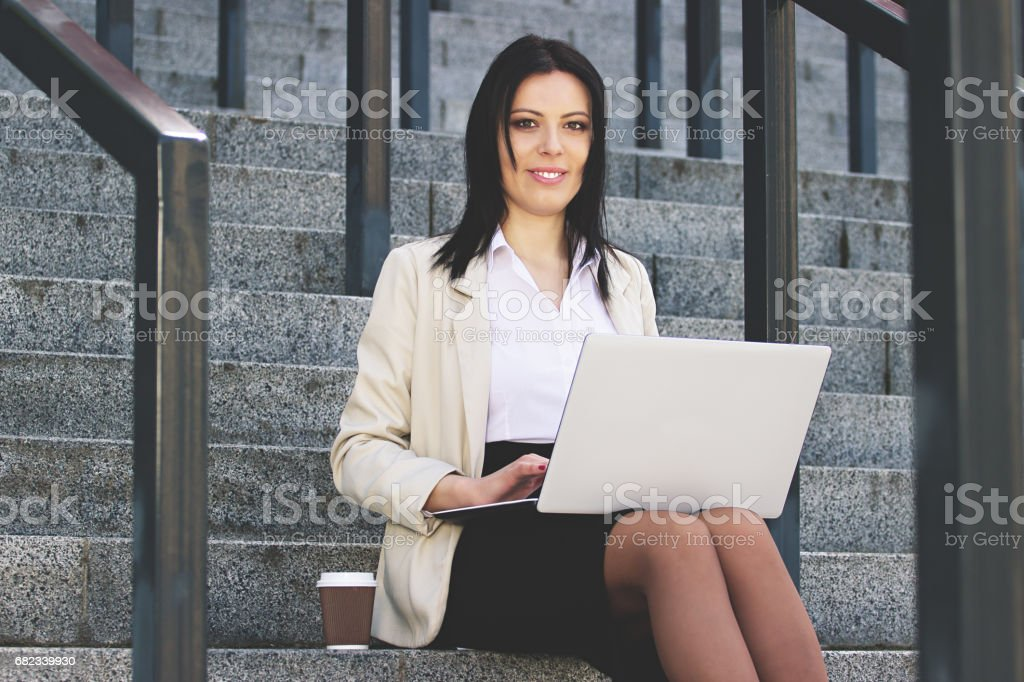 Working at every moment. Portrait of cheerful attractive business woman in smart casual wear working with laptop while sitting near office building. foto stock royalty-free