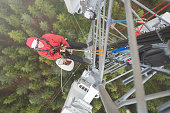 Telecommunication manual high worker engineer installing new 3g 4g LTE antenna on tall mobile base station (communication tower) in the middle of european forest, high angle of view. Working at height. Telecommunication masts and towers are typically tall structures designed to support antennas for telecommunications and broadcasting. Drone point of view.