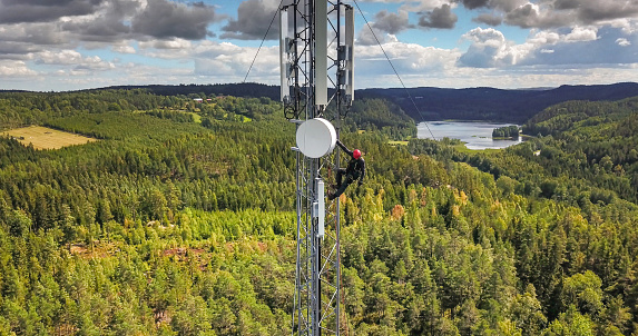 Telecommunication manual high worker engineer installing new 4g, 5g LTE antenna on tall mobile base station (communication tower) in the middle of european forest. Working at height. Telecommunication masts and towers are typically tall structures designed to support antennas for telecommunications and broadcasting. Drone point of view.