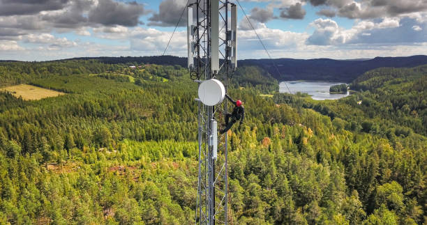 Working at height Telecommunication manual high worker engineer installing new 4g, 5g LTE antenna on tall mobile base station (communication tower) in the middle of european forest. Working at height. Telecommunication masts and towers are typically tall structures designed to support antennas for telecommunications and broadcasting. Drone point of view. antenna aerial stock pictures, royalty-free photos & images