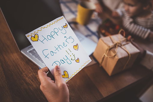 istock Working at home father holding father's day card and gift 983431494