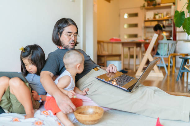 Working at home father with his children A stay-at-home father is taking care of his children and working on a laptop in the living room at home. One of his daughters is doing her homework in the background. stay at home father stock pictures, royalty-free photos & images