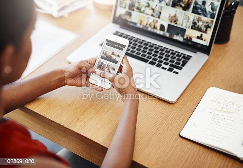 Cropped shot of an unrecognizable businesswoman using a cellphone in her home office