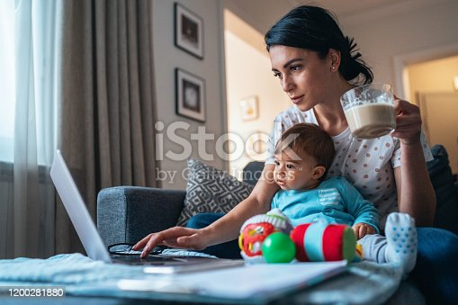 Young modern mother with a baby using laptop at home