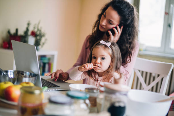 Working at home Mother work at home with little girl еating messy home office stock pictures, royalty-free photos & images