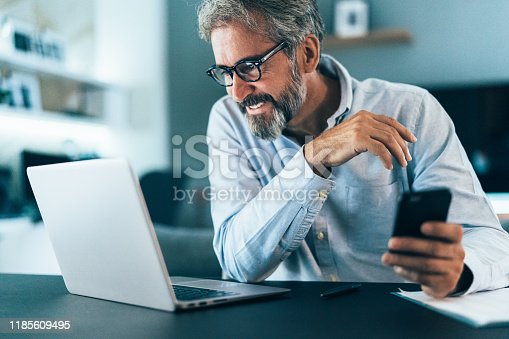 Mature businessman working at home using lap top and smart phone