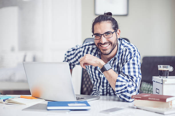 Working at home Young man is working at home man bun stock pictures, royalty-free photos & images