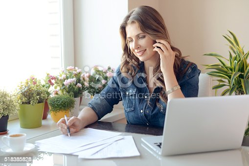 young beautiful woman sitting at the table and working at home