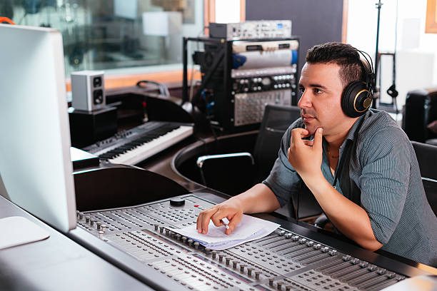 Working at mixing panel Hispanic sound engineer working at mixing panel in the recording studio producer stock pictures, royalty-free photos & images