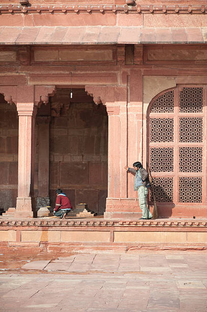 Working at mosque in Fatehpur Sikri, India Fatehpur Sikri, India - January 10, 2011: A boy cleaning tombs at Jama Masjid mosque in Fatehpur Sikri, India. An adult is taking a rest, overseeing his work. A broomstick leaning against the wall.  Jama Masjid mosque is located next to the ghost town of Fatehpur Sikri and was built in 1571. It is used for worship and community service. People fulfill small services at temples and mosques for food and shelter, considering these as religious offerings and making a living. agra jama masjid mosque stock pictures, royalty-free photos & images