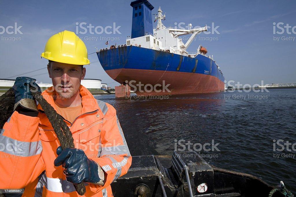Working at the harbor between big cargo ships. stock photo