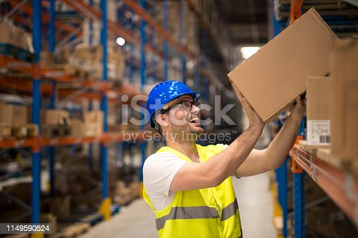 Happy warehouse worker relocating boxes in storage compartment.