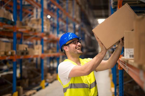 werken bij warehouse. glimlachend magazijn werknemer verhuisdozen op de plank. - warehouse worker stockfoto's en -beelden