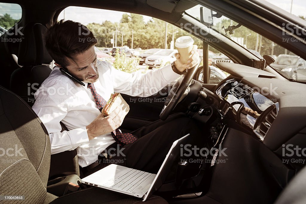 Working businessman eating inside car stock photo