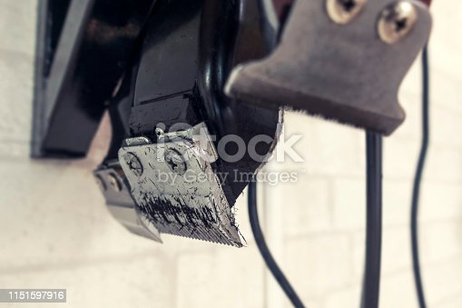 1147090180 istock photo A working clipper with cuted hair hanging in the barber background 1151597916