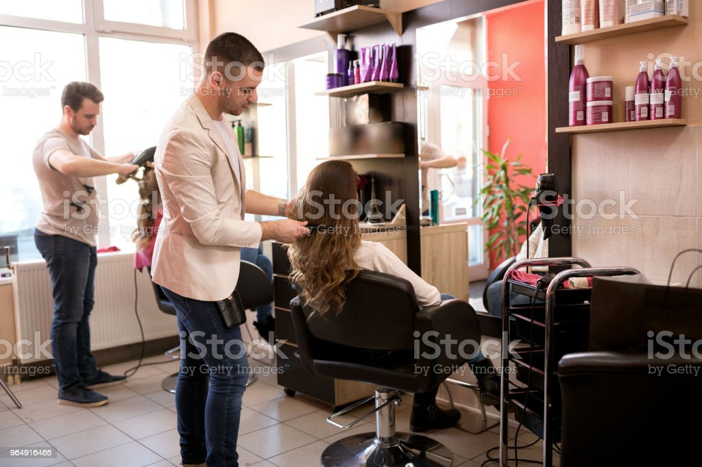 Working day inside the hair salon, hairdresser care of customer hair royalty-free stock photo