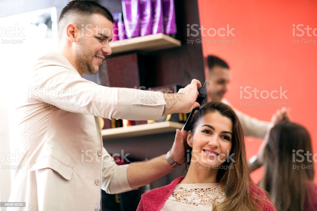 Working day inside the hair salon, hairdresser cutting woman's hair at salon royalty-free stock photo