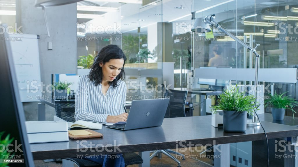 Working Day of a Beautiful Hispanic Businesswoman. She Works on Laptop Alone in an International Office. royalty-free stock photo