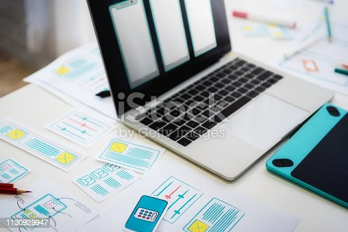 1182469817istockphoto Working desk of programmer developing technologies mobile phone with sketch application on table. User experience concept. 1130929947