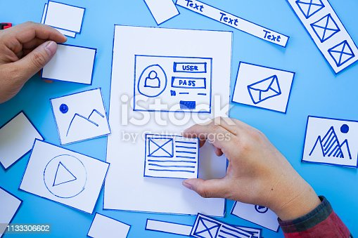 1182469817 istock photo Working desk with hands sorting wireframe screens of mobile responsive website. Developing wireframe sketch layout design mockup on smartphone,tablet screen. 1133306602