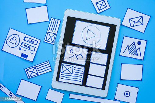 1182469817 istock photo Working desk with hands sorting wireframe screens of mobile responsive website. Developing wireframe sketch layout design mockup on smartphone,tablet screen. 1133306703