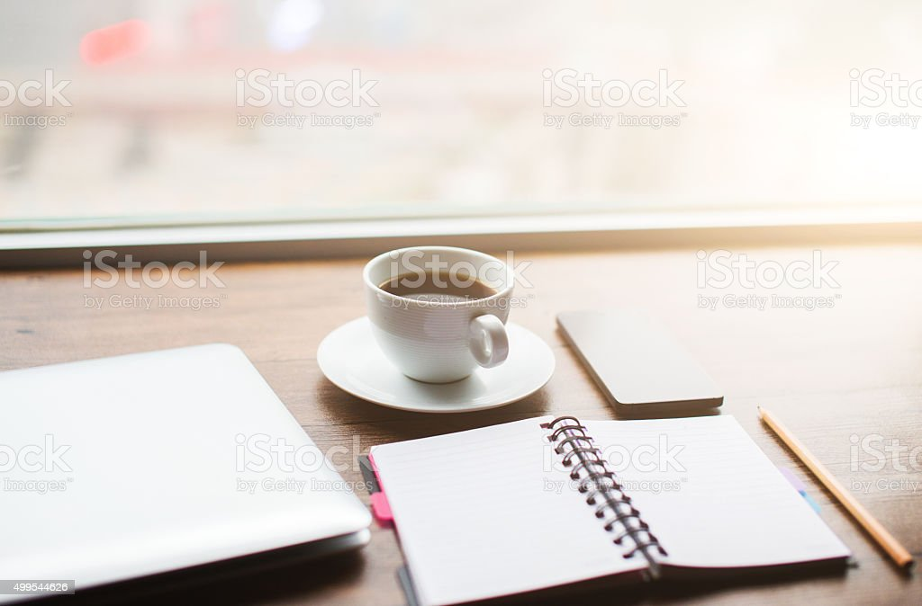 Working desk with laptop,notebook and coffee