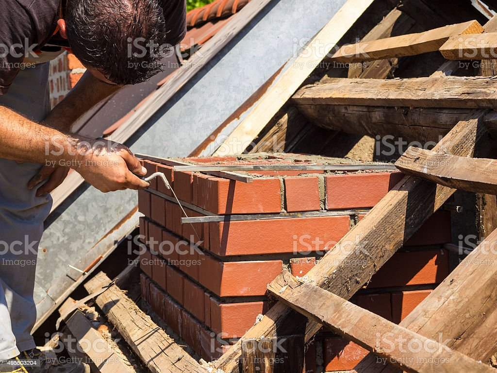 Working detail on brick chimney on an old roof stock photo