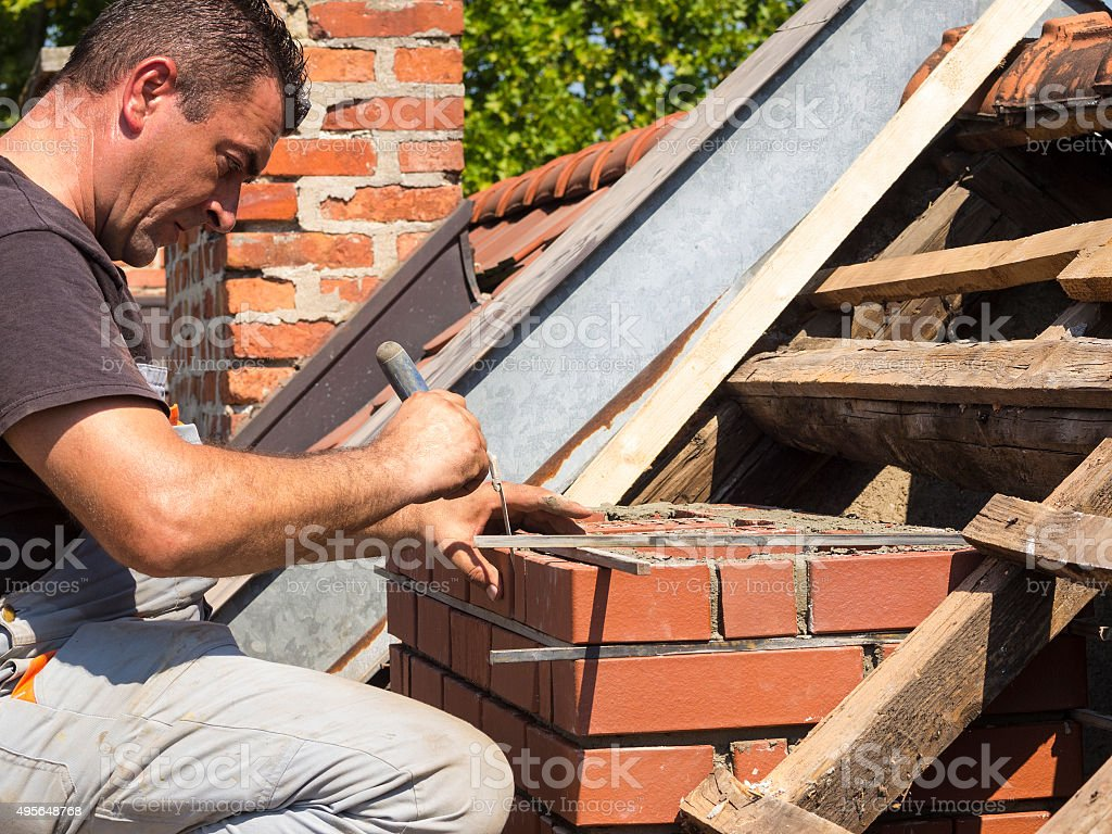 Costruire Tetto In Cemento working detail on brick chimney on an old roof stock photo