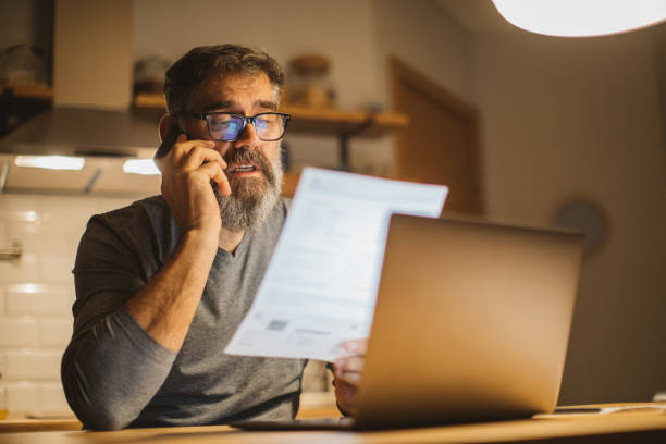 Working during isolation period Mature men at home during pandemic isolation reading something on laptop bills and taxes stock pictures, royalty-free photos & images
