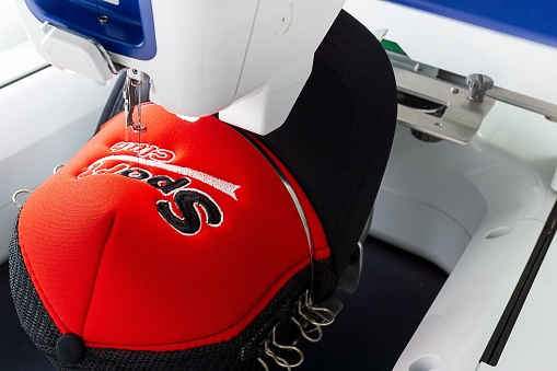 Close up image of white embroidery machine embroidering logo on red and black sport cap
