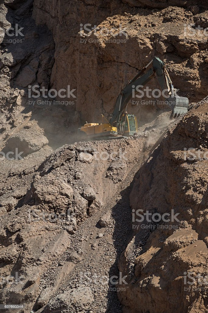 Working excavator in mountains stock photo