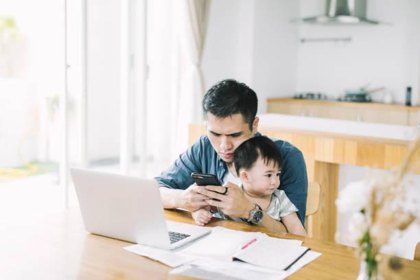 arbetande far med söt son med hjälp av mobil telefon - working from home bildbanksfoton och bilder