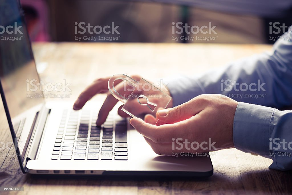Working for a more sequre internet experience Closeup of man tying on a laptop keyboard while holding on one hand a lock like transparent object. Focus is on the lock symbol meaning online information security Antivirus Software Stock Photo