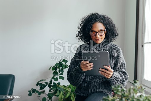 Young woman wearing glasses watching something on her digital tablet (copy space).