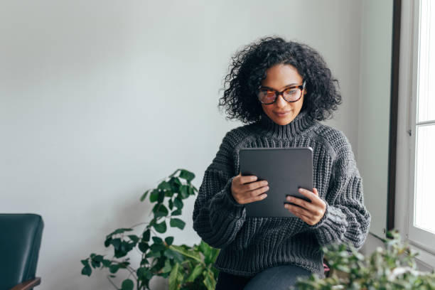Working from Home: a Young Woman USing a Digital Tablet to Read/Watch Something Young woman wearing glasses watching something on her digital tablet (copy space). ipad stock pictures, royalty-free photos & images