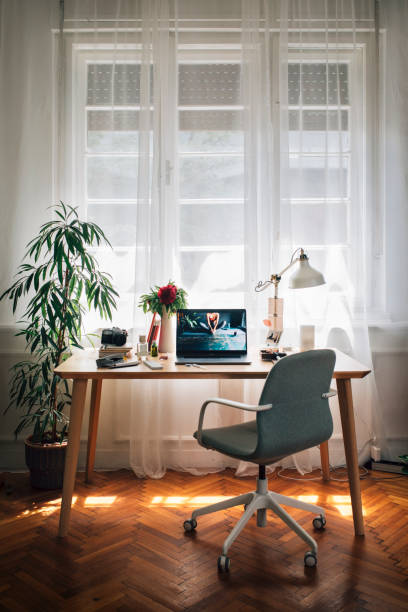 Working from Home: an Improvised Home Office of a Businesswoman, Laptop on the Desk Social distancing: the cosy workplace of a businesswoman working from home. messy home office stock pictures, royalty-free photos & images