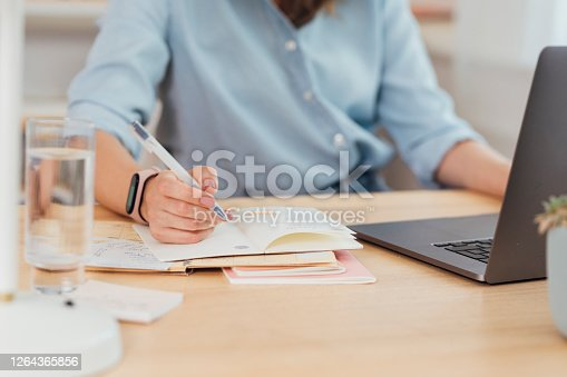 Anonymous woman working at her home office - writing notes and using a laptop pc, a close up.