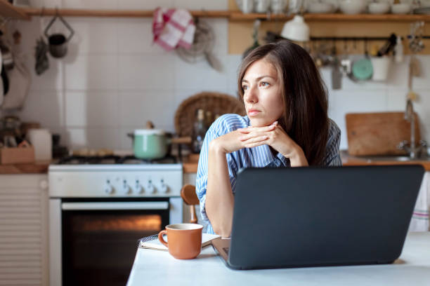 Working from home office. Upset woman using laptop and Internet. Freelancer workplace at kitchen table. stock photo