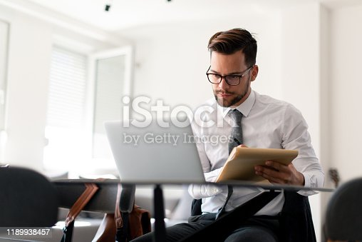 Formally dressed guy is working from home on a laptop.